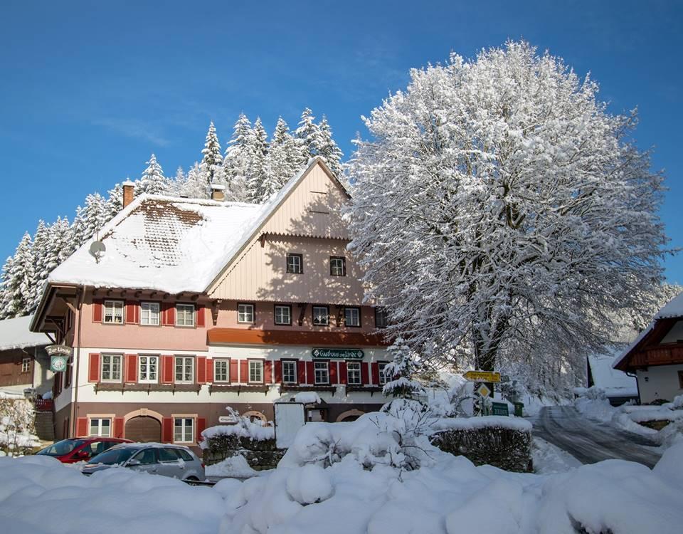 Gasthaus Zur Linde mit verschneitem Lindenbaum im Winter